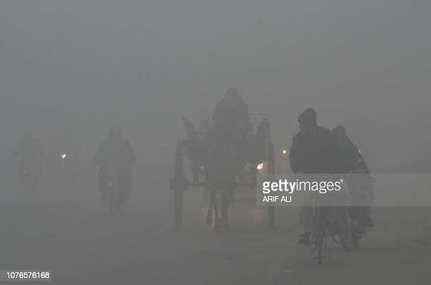 TOPSHOT Pakistani commuters drive their vehicles on a road amid heavy fog and smog conditions in Lahore on January 3 2019 Smog levels spike during...