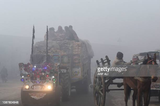 TOPSHOT Pakistani commuters drive their vehicles on a road amid heavy fog and smog conditions in Lahore on January 24 2019 Smog levels spike during...