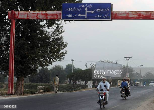 Pakistani commuters ride past road signage following the execution of Ajmal Kasab who was hanged in an Indian prison at Kasab's village in Farid kot...