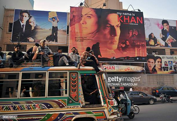 Pakistani commuters sitting on top of a bus pass by a cinema screening Indian Bollywood actor Shah Rukh Khan's film 'My Name is Khan' in Karachi on...