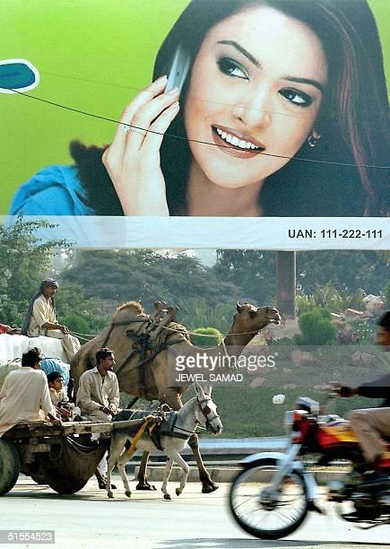 STORY PAKISTANTELECOM Pakistani commuters using various modes of transportation make their way past an advertisement billboard promoting hitech...