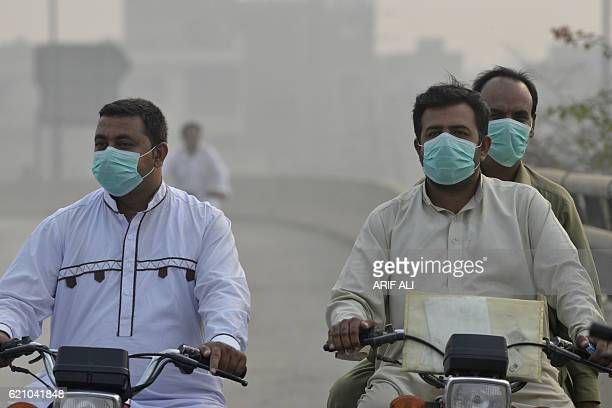 Pakistani commuters wear masks as heavy smog envelops the city in Lahore on November 4 2016 The Pakistan Meteorological Department has forecast...