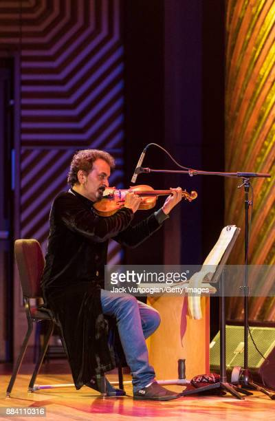 Pakistani conductor and musician Nijat Ali plays violin as he leads the Sachal Jazz Ensemble in a performance during a World Music Institute concert...