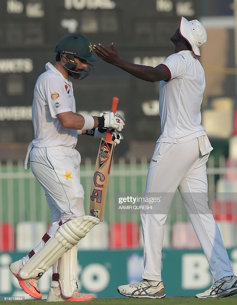 Pakistani cricket captain Misbah-ul-Haq (L) back to pavilion after his dimissal next to West Indies' captain Jason Holder on the first day of the third and final Test between Pakistan and West Indies at the Sharjah Cricket Stadium in Sharjah on October 30, 2016. Pakistan captain Misbah-ul-Haq won the toss and opted to bat against West Indies in the third and final Test in Sharjah. / AFP / AAMIR