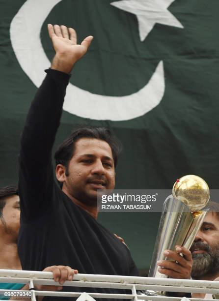 Pakistani cricket captain Sarfaraz Ahmed acknowledges fans as he holds the Champions Trophy following his arrival from London in Karachi on June 20...