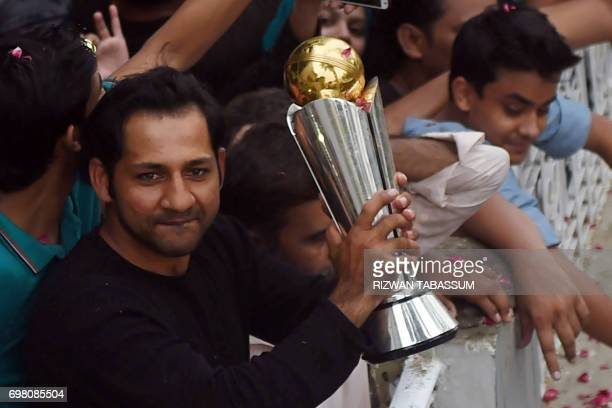 Pakistani cricket captain Sarfaraz Ahmed holds the trophy as he acknowledges fans at his home following his arrival from London in Karachi on June 20...