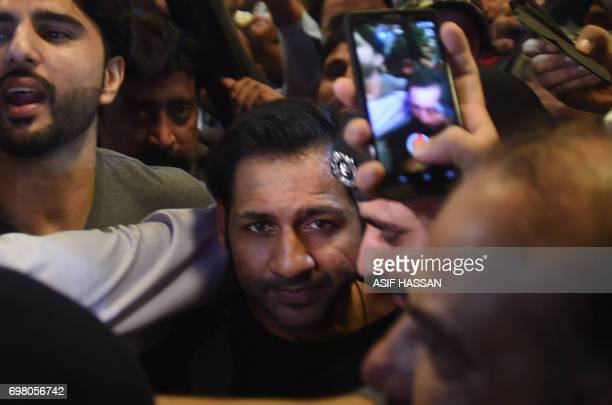 Pakistani cricket captain Sarfaraz Ahmed is surrounded by fans as he arrives from London outside the Karachi International airport in Karachi on June...