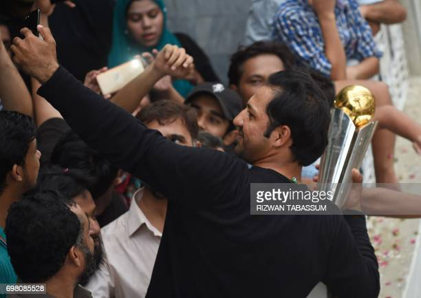 Pakistani cricket captain Sarfaraz Ahmed takes a selfie while holding the trophy as he acknowledges fans at his home following his arrival from...