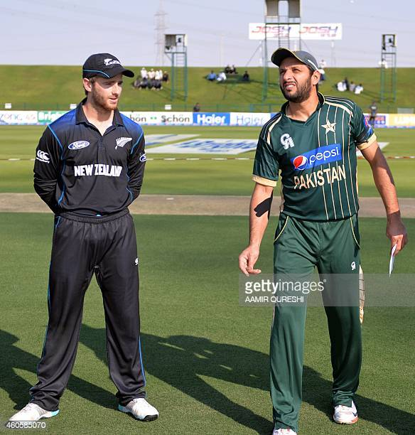 Pakistani cricket captain Shahid Afridi tosses a coin as he stands next to his New Zealand counterpart Kane Williamson before the start of the fourth...