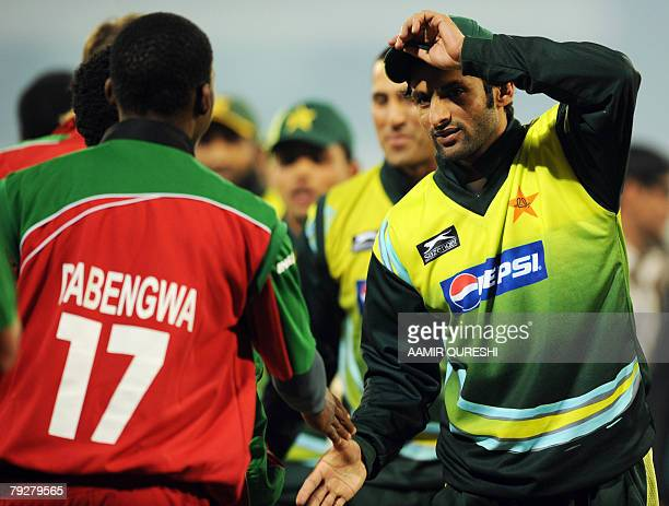 Pakistani cricket captain Shoaib Malik shakes hands with Zimbabwean cricketer Keith Dabengwa at the end of the third OneDay International cricket...