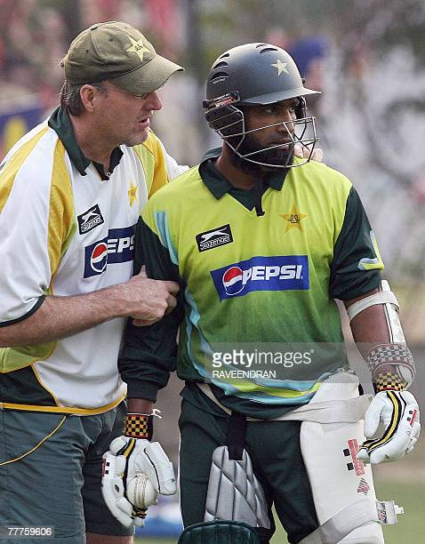 Pakistani cricket coach Geoff Lawson chats with cricketer Mohammad Yousuf during a training session at the Mohali Cricket Stadium in Mohali 07...