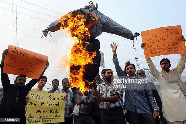 A Pakistani cricket fan holds a burning effigy of London's Southwark Crown Court judge Jeremy Cooke during a protest in Lahore on November 4 2011 to...