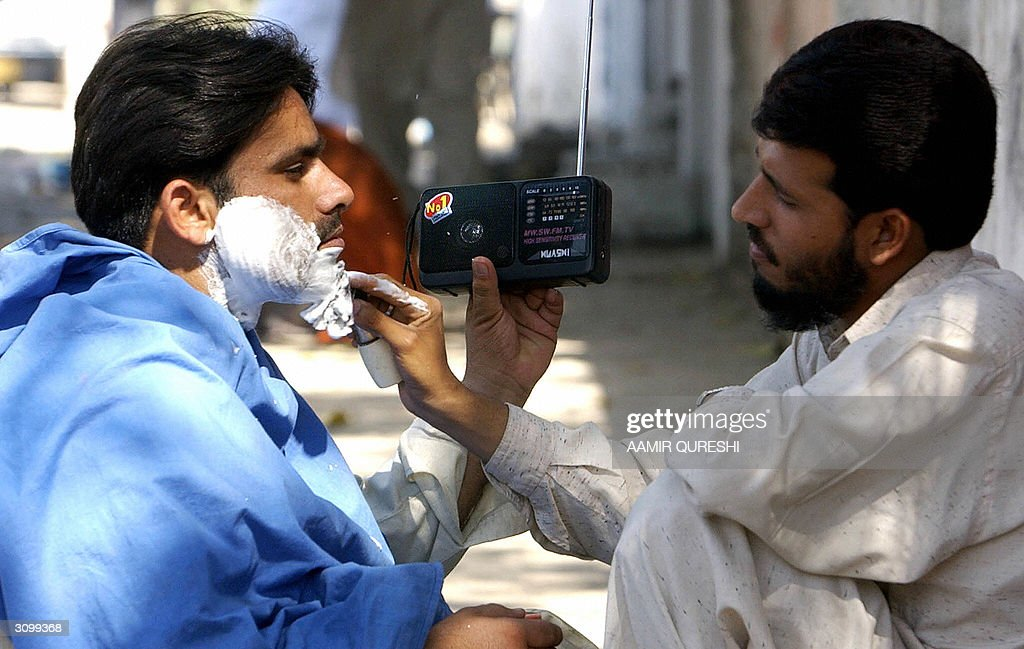 A Pakistani cricket fan (L) listens to radio coverage of the India-Pakistan one-day international match while being shaved at a roadside barber in Karachi, 16 March 2004. The Indian cricket team last toured Pakistan in 1989 and the ongoing series has frenzied fans in both countries. AFP PHOTO/Aamir QURESHI