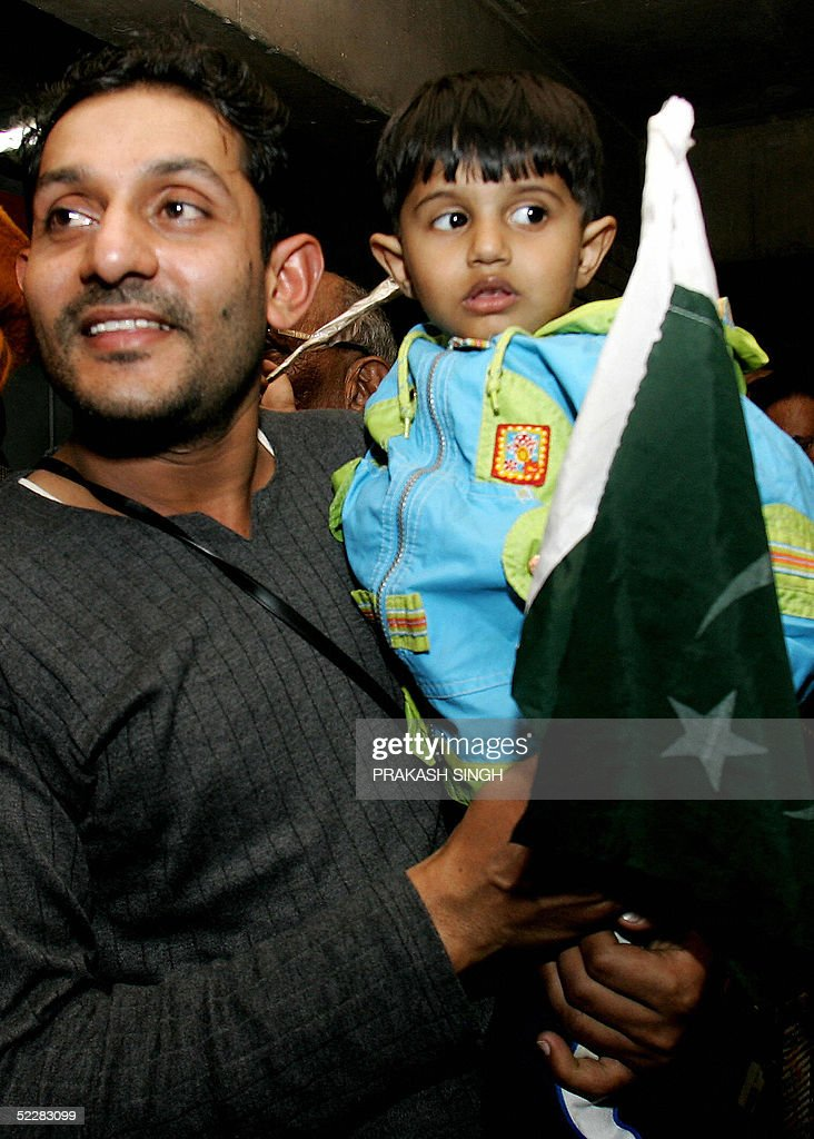 Pakistani cricket fan Naeem poses with his nephew Ali who holds a Pakistani flag after they arrived by bus in Chandigarh 06 March 2005 to watch the...