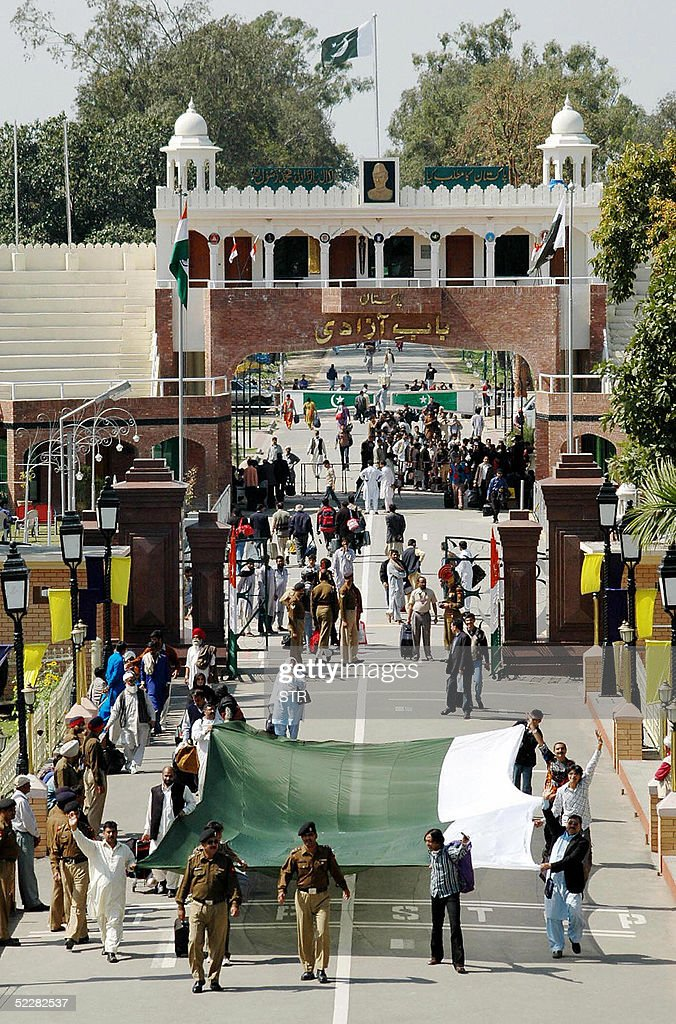 Pakistani cricket fans are escorted by security personnel as they carry a flag after crossing into India at the Wagah Border Post 06 March 2005 to...