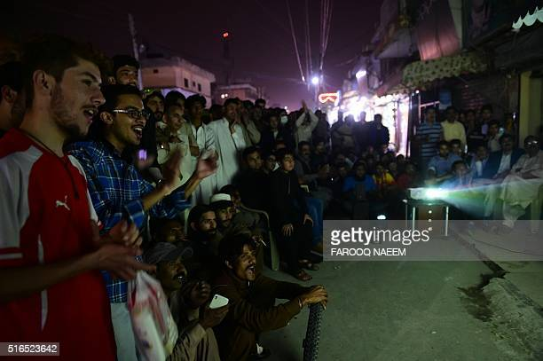 Pakistani cricket fans gather around screen on a street in Rawalpindi on March 19 as they watch the World T20 cricket tournament match between India...