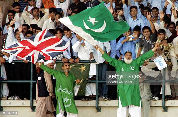 Pakistani cricket fans hold flags of England and Pakistan during the fourth day of the first Test match in Multan Cricket Stadium 15 November 2005...