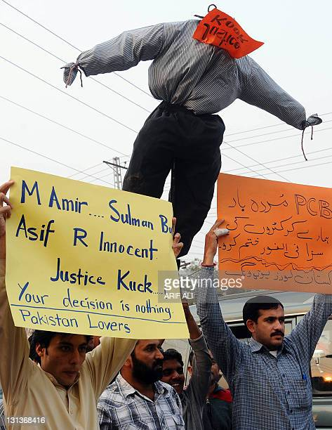 Pakistani cricket fans hold placards and an effigy of London's Southwark Crown Court judge Jeremy Cooke during a protest in Lahore on November 4 2011...