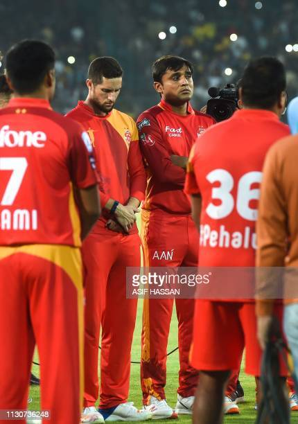 Pakistani cricket players of Islamabad United stand silent to pay tribute to the victims of the two mosques attacked in New Zealand in Karachi on...