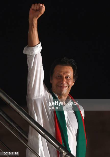 Pakistani cricket starturnedpolitician and head of the Pakistan TehreekeInsaf Imran Khan raises his fist during a political campaign rally for the...