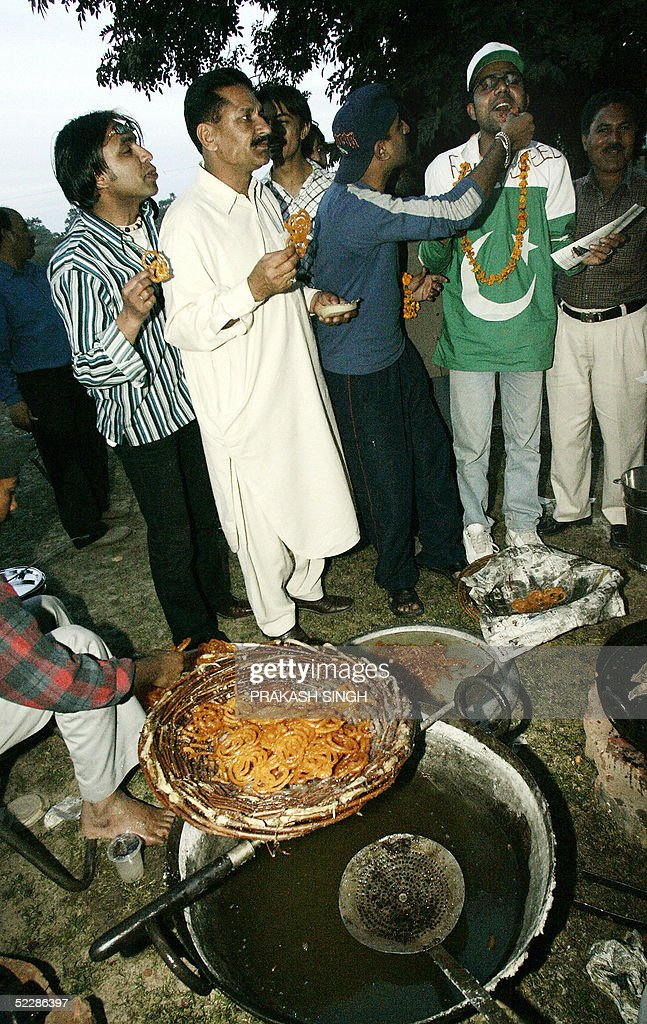 Pakistani cricket supporters are welcomed by Indian supporters with sweets after their buses arrived in Chandigarh 07 March 2005 Hundreds of...
