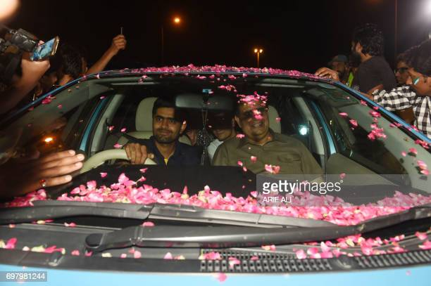 Pakistani cricketer Babar Azam is surrounded by fans as he drives his car upon his arrival from London outside the Allama Iqbal International airport...
