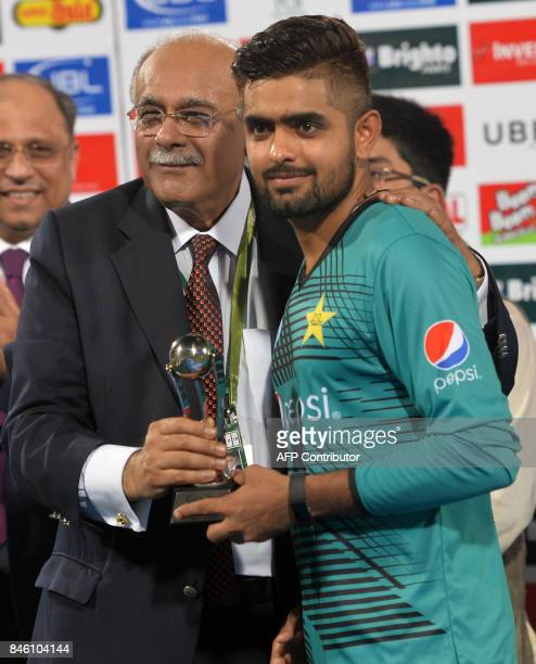 Pakistani cricketer Babar Azam receives man of the match award from Chairman Pakistan Cricket Board Najam Sethi during a ceremony at the end of the...
