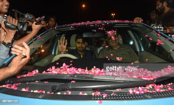 Pakistani cricketer Babar Azam waves as he drives his car upon his arrival from London outside the Allama Iqbal International airport in Lahore on...