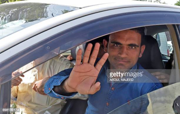 Pakistani cricketer Fakhar Zaman gestures upon his arrival from London outside the Bacha Khan International airport in Peshawar on June 20 after...