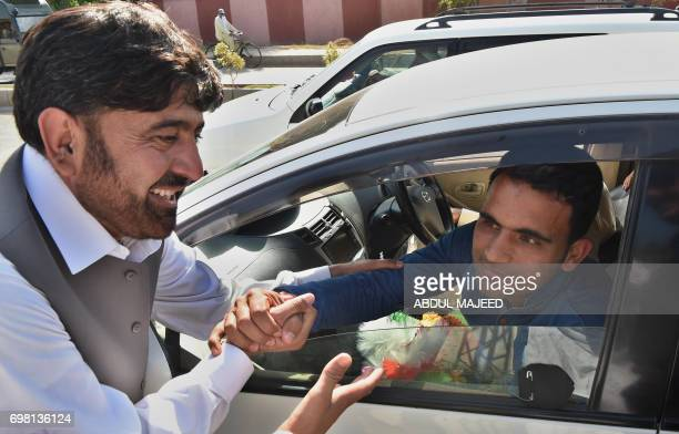 Pakistani cricketer Fakhar Zaman greets a supporter upon his arrival from London outside the Bacha Khan International airport in Peshawar on June 20...