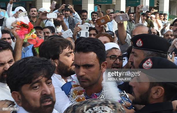 Pakistani cricketer Fakhar Zaman is surrounded by fans as he arrives from London outside the Bacha Khan International airport in Peshawar on June 20...