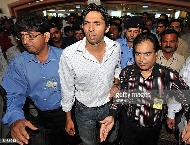Pakistani cricketer Mohammad Asif is escorted by security officials as he leaves the arrivals hall at Allama Iqbal International Airport in Lahore on...