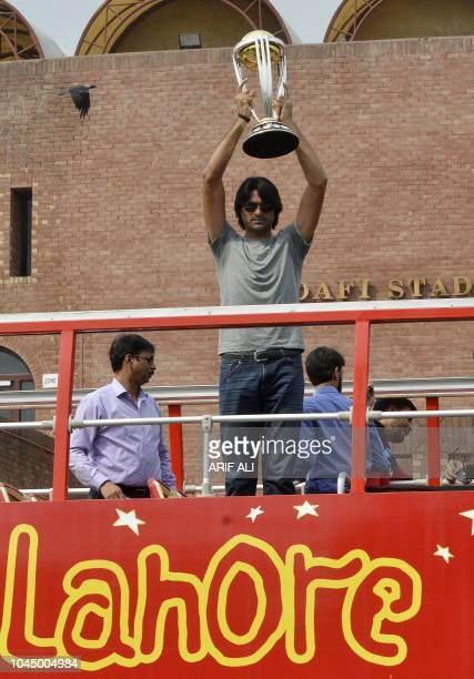 Pakistani cricketer Mohammad Irfan holds the 2019 ICC Cricket World Cup trophy atop a bus during a parade event in Lahore on October 3 2018 The 2019...