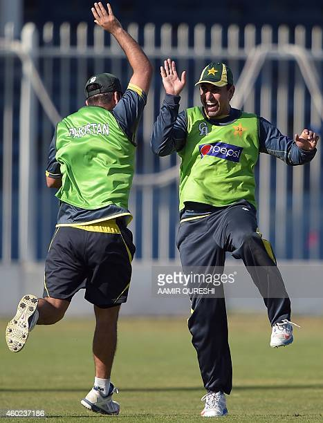 Pakistani cricketer Nasir Jamshed shares a light moment with teamate Ahmed Shehzad during a practice session at the Sharjah cricket stadium in...
