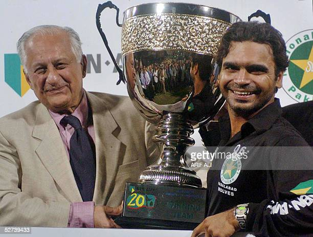 Pakistani cricketer Naveed Latif captain of the Faisalabad Wolves receives a winning trophy from Pakistan Cricket Board Chairman Shaharyar Khan at...