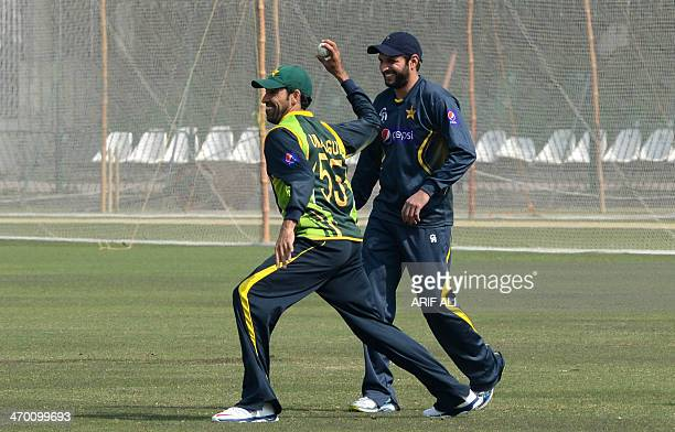 Pakistani cricketer Shahid Afridi watches as Umar Gul bowls during a team practice in the training camp at the Gaddafi stadium in Lahore on February...