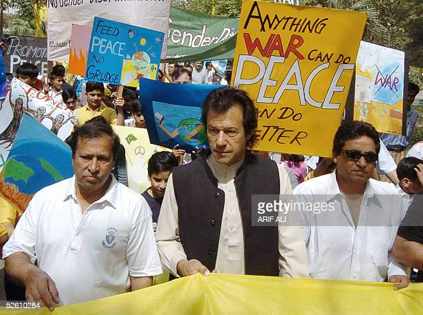 Pakistani cricketer turned politician Imran Khan and film director Syed Noor hold a banner during a walk demonstrating against violence towards women...