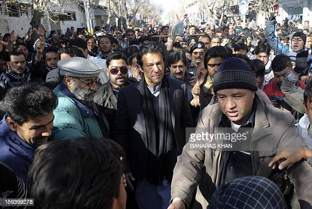 Pakistani cricketer turned politician Imran Khan walks as he arrives to meet demonstrators of Shiite Muslim families who refusing to bury their dead...