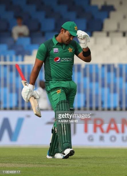Pakistani cricketer Umar Akmal leaves the field after being dismissed by Australia cricketer Nathan Lyon during the second one day international...