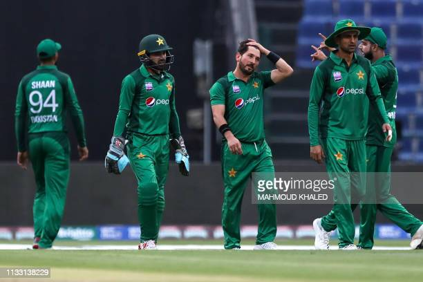 Pakistani cricketer Yasir Shah celebrates with his teammates the dismissal of Australian cricketer Aaron Finch during the third one day international...
