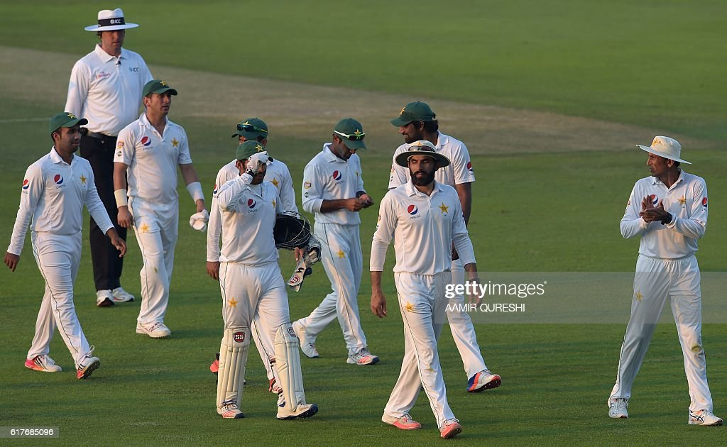 Pakistani cricketers backs to pavilion at the end of the fourth day of the second Test between Pakistan and the West Indies at the Sheikh Zayed Cricket Stadium in Abu Dhabi on October 24, 2016. Pakistan pressed West Indies hard for a series-clinching win in the second Test after setting a daunting 456-run target on the fourth day in Abu Dhabi. By close of play Pakistan had taken four wickets at 171 leaving the West Indies to bat out the fifth and final day on October 25 or score a further 285 runs with six wickets intact for an unlikely win. / AFP / AAMIR