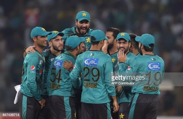 Pakistani cricketers celebrate after dismissal of World XI batsman Hashim Amla during the third and final Twenty20 International match between the...