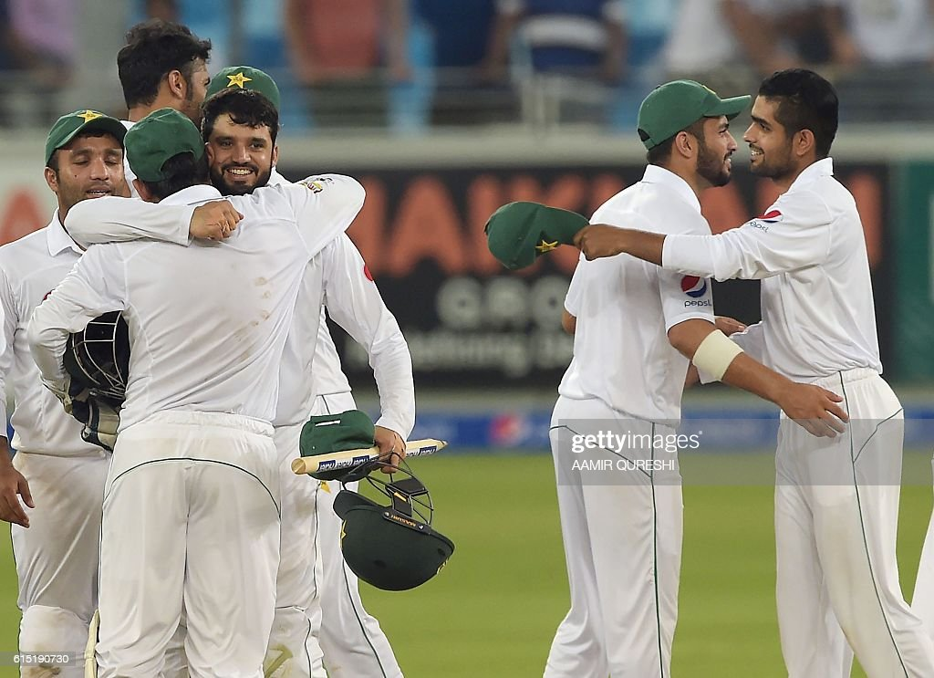 Pakistani cricketers celebrate after winning first day-night Test between Pakistan and the West Indies at the Dubai International Cricket Stadium in the Gulf Emirate on October 17, 2016. Pakistan beat West Indies by 56 runs in the first day-night Test on the fifth and final day in Dubai on October 17, taking a 1-0 lead in the three-match series. / AFP / AAMIR