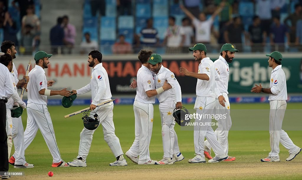 Pakistani cricketers celebrate after winning the first day-night Test between Pakistan and the West Indies at the Dubai International Cricket Stadium in the Gulf Emirate on October 17, 2016. Pakistan beat West Indies by 56 runs in the first day-night Test on the fifth and final day in Dubai on October 17, taking a 1-0 lead in the three-match series. / AFP / AAMIR