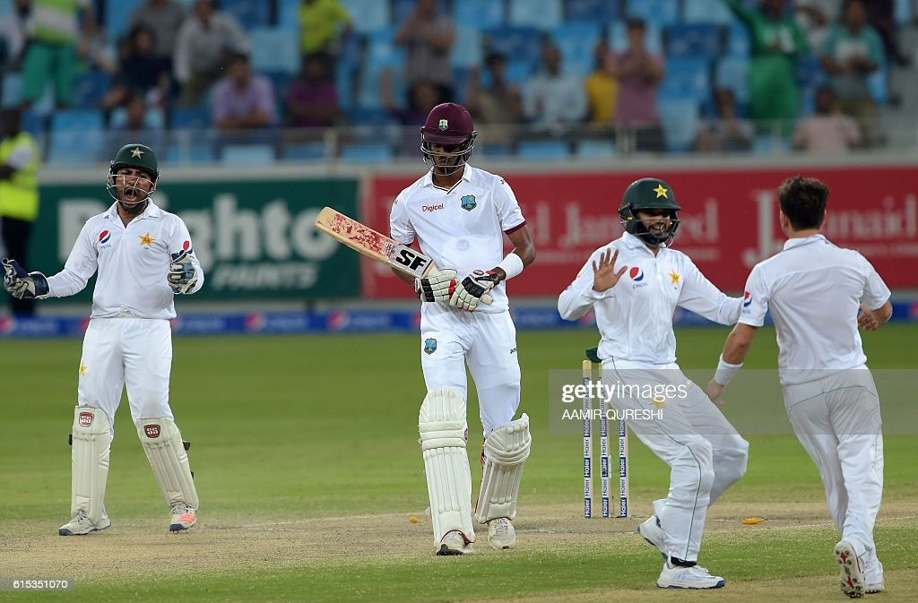 Pakistani cricketers Sarfraz Ahmed (L), Azhar Ali (2R) and Yasir Shah (R) celebrate after dismissing West Indies' batsman Roston Chase (2L) on the final day of the first day-night Test between Pakistan and the West Indies at the Dubai International Cricket Stadium in the Gulf Emirate on October 17, 2016. / AFP / AAMIR
