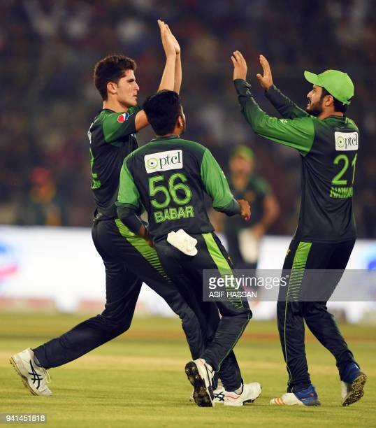 Pakistani cricketers Shaheen Afridi Mohammad Nawaz and Babar Azam celebrate after the dismissal of West Indies captain Jason Mohammed during the...
