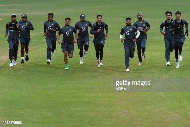 Pakistani cricketers warm up during a team practice session at the Gaddafi Cricket Stadium in Lahore on October 14 ahead of the ICC men's Twenty20...