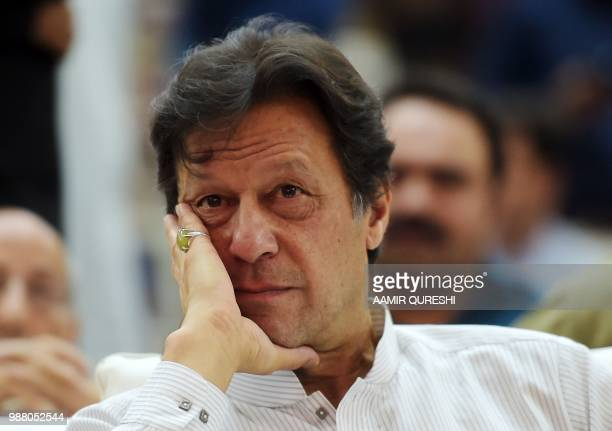 Pakistani cricketer-turned-politician and head of the Pakistan Tehreek-i-Insaf Imran Khan looks on as he attends an election campaign rally in...