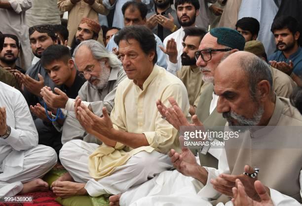 Pakistani cricketerturnedpolitician and head of the Pakistan TehreekiInsaf Imran Khan prays with elder brother Aslam Raisani of Siraj Raisani a...