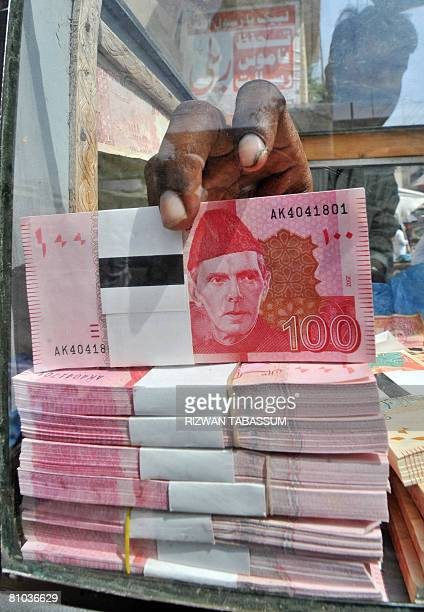 A Pakistani currency dealer adjusts rupee at a road side stall in Karachi on May 9 2008 The Pakistani rupee saw its biggest fall in five years May 9...